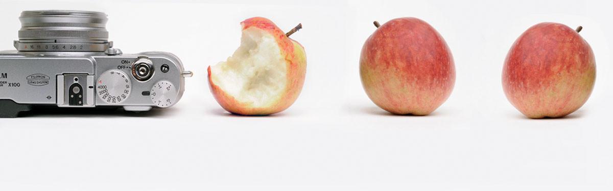 Das Bild zeigt eine Kamera mit drei Äpfeln