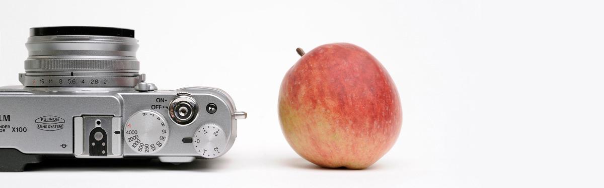 Das Foto zeigt einen Apfel neben einer Kamera liegend.