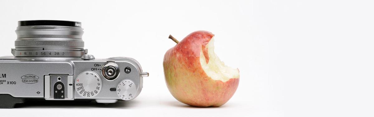 Das Foto zeigt einen angebissenen Apfel auf einem aufgeschlagenen Buch neben einer Kamera liegend.
