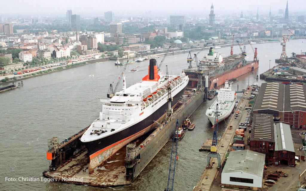 """Beispiel für eine Bildbeschreibung, mit der das Foto zu verwerten ist: """"Das Archivfoto, aufgenommen am 8.9.1992 in Hamburg, zeigt eine Luftaufnahme der """"Queen Elizabeth 2"""". Das Luxuskreuzfahrtschiffes liegt im Schwimmdock der Werft HDW an der Elbe in Hamburg zur Überholung liegt. (Nordbild / Christian Eggers)"""