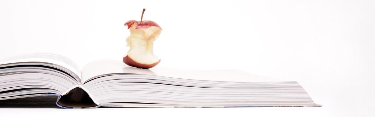 Das Foto zeigt einen angebissenen Apfel auf einem aufgeschlagenen Buch liegend.